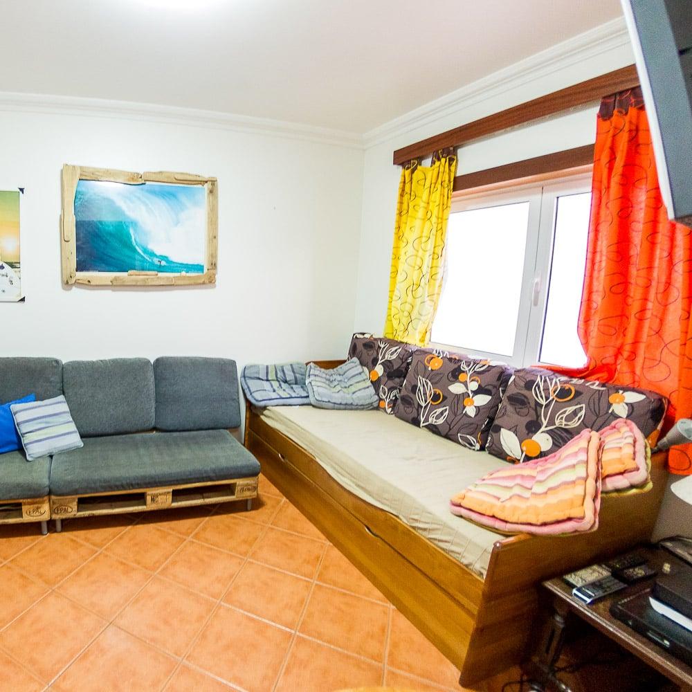 Palettensofas, Kabel TV und Esstisch im Wohnzimmer vom Surfcamp